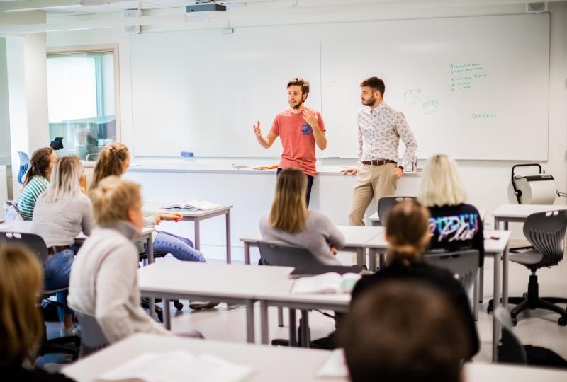 Foto av to menn som står foran fleire elevar